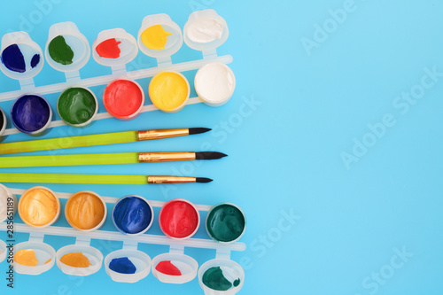 Slika na platnu Colorful paints in jars on a blue background near the brushes