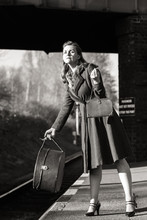 An Elegant 40s Lady Awaits Her Train At Quorn And Woodhouse With Her Luggage.