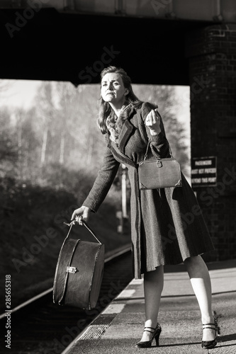 An elegant 40s lady awaits her train at Quorn and Woodhouse with her luggage Canvas Print
