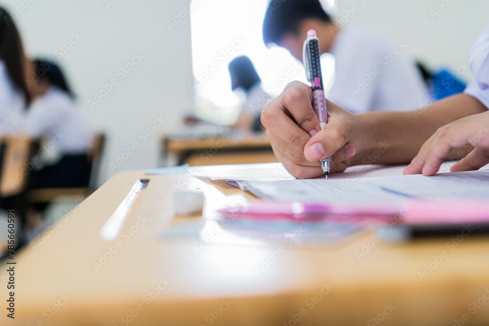 Fototapeta Education uniform students testing exam with pencil for multiple-choice quizzes or testing exams answer sheets exercises in school rows chairs at classroom in Thailand