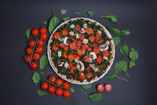 Pizza Vegana Con Espinacas, Tomates Cherry Y Champiñones Sobre Fondo Negro.