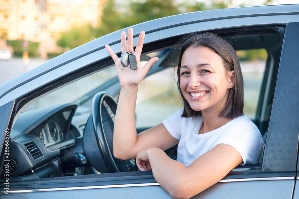 Fototapeta Portrait of confident young woman in the new car