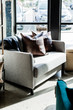 Grey loveseat couch with pillows and blanket