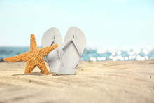 Starfish And Flip Flops On Sand Near Sea, Space For Text. Beach Objects
