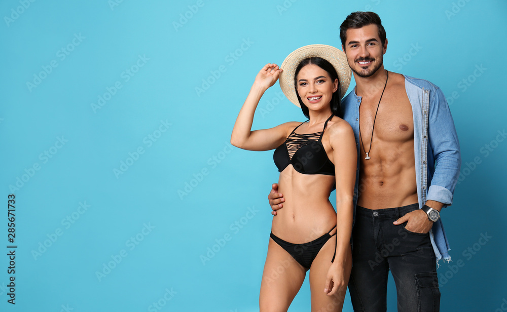 Beautiful young woman in stylish bikini and man on light blue background. Space for text
