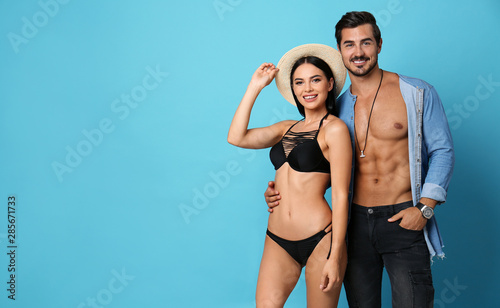 Fototapety, obrazy: Beautiful young woman in stylish bikini and man on light blue background. Space for text