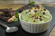 canvas print picture Delicious green ice cream served in ceramic bowl on table