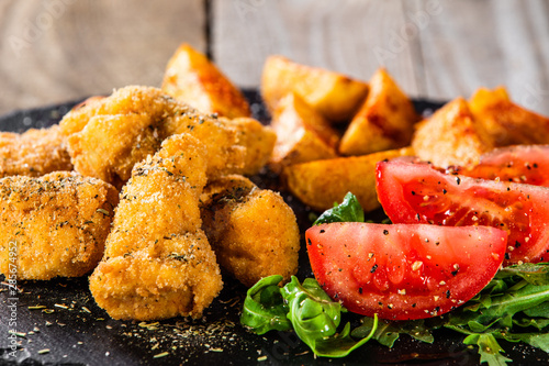 Poster Appetizer Fried chicken nuggets, baked potatoes and vegetable salad
