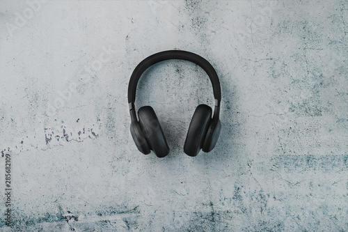 Wireless black headphones on a dark background with blue and orange backlight. On-ear headphones for playing games and listening to music tracks - 285682109