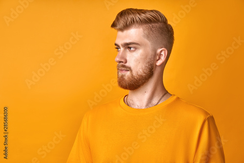 Fotografía  Profile shot of handsome male with trendy hairdo and red beard, looks aside with