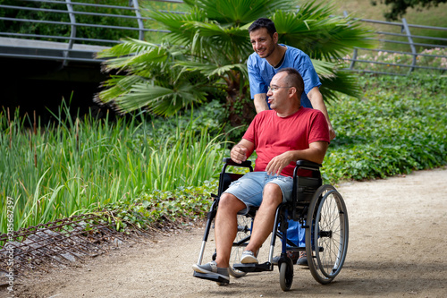 Fotomural disabled man in a wheelchair talking with his caretaker