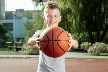 Portrait Of A Boy With A Basketball On A Basketball Court. The Concept Of A Sports Lifestyle, Training, Sport, Leisure, Vacation.