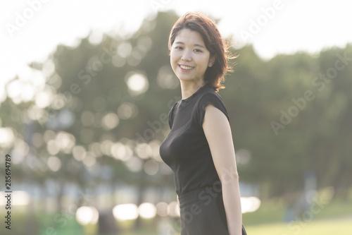 Fotografía 海沿いの公園を歩く若い女性