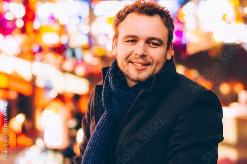 Photo  Closeup portrait of a young man in a coat and scarf, a man walks through the evening city lit by lights