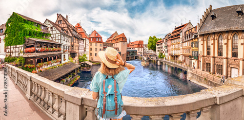 Young girl with backpack standing on a bridge over d Ill river in Strasbourg, France #285711198