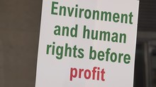"""A Protest Placard With Green And Red Writing Says, """"Environment And Human Rights Before Profit""""."""