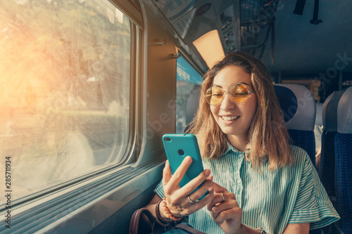 Obraz Happy Asian girl using transport application on smartphone while travelling by high speed train - fototapety do salonu