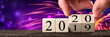 canvas print picture Hand Changing Date From 2019 To 2020 On Wooden Cube Calendar With Fireworks In Background / New Year's Concept