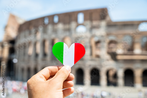 Obraz na plátne Woman Holding Heart Shaped Italian Flag In Front Of Colosseum