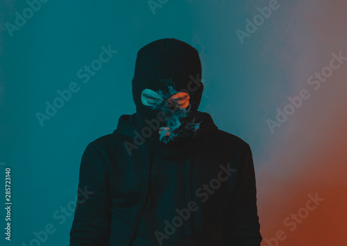 Photo young man in hoodie and balaclava looking down and blow smoke out