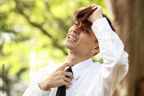 タオルで汗を拭う男性社員 Fototapet