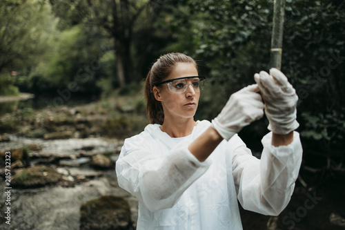Female scientist biologist and researcher in protective suit taking water samples from polluted river Wallpaper Mural