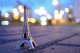 Fototapeta Fototapety z wieżą Eiffla - Eiffel tower figure on a background of evening bokeh lights. Located on the paving stones, asphalt.