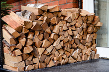 Stacked Firewood. A Brick Wall In The Background.
