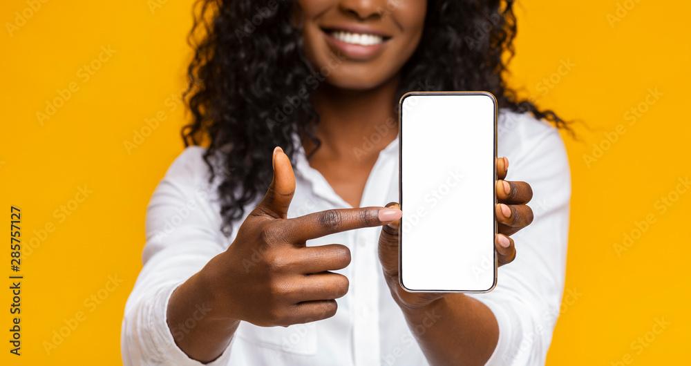 Fototapeta Happy black woman holding latest slim smartphone