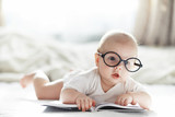 A newborn baby is lying on a soft bed in glasses. - 285763589