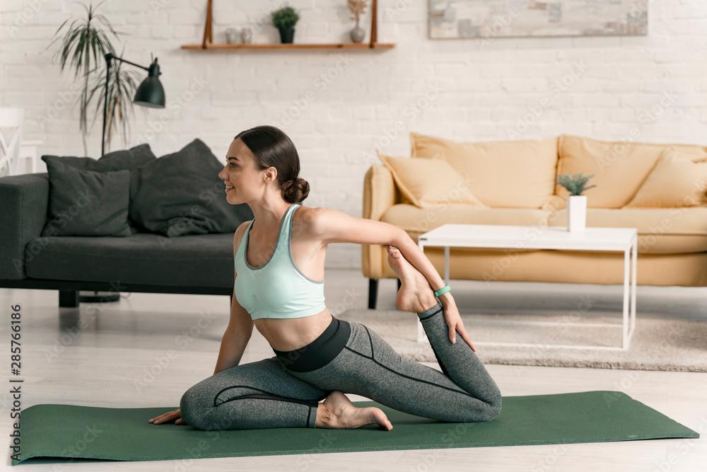Fototapety, obrazy: Smiling female stretching legs indoors stock photo