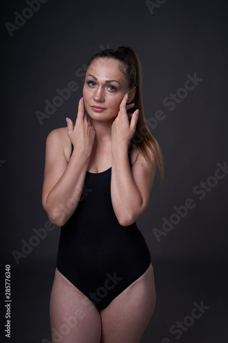 Photo flexible sexy girl poses on a black grey background in the fitting clothes baud