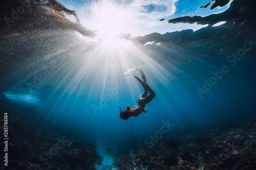 Fotobehang Duiken Free diver woman with fins over coral bottom and amazing sun rays.