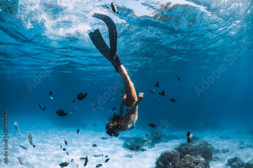 Woman freediver with fins over sandy sea with fishes