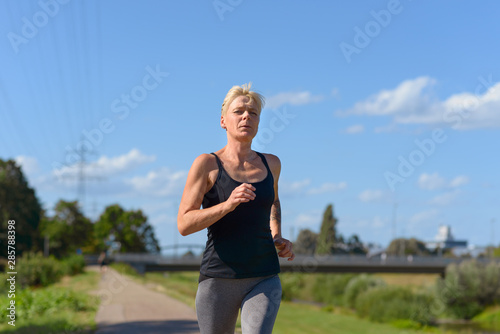 Canvas-taulu Woman jogging outdoors in summer sunshine