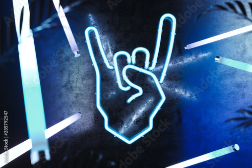 Hand in rock and roll sign made from neon lamps on dark background Canvas Print