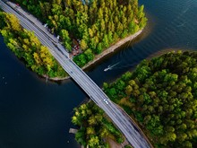 Aerial View Of The Bridge With A Boat Passing Under It. Blue Lake With Summer Houses In Finland.