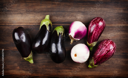 Tablou Canvas Fresh eggplants of different color and variety on a wooden background
