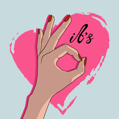 Ok hand with red nail polish on the background of a pink heart. Hand gesture, ok. Woman showing okay hand gesture. It's ok.