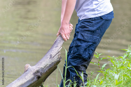 Fotografie, Tablou  Europäischer Junge hebt mit beiden Händen einen Baumstamm am Flussufer hoch und