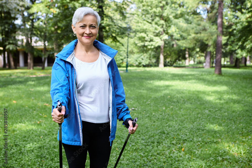 Fototapety, obrazy: Happy energetic active female pensioner in blue jacket enjoying Nordic walking using specially designed poles, breathing fresh air outdoors. Physical activity, healthy lifestyle, people and aging