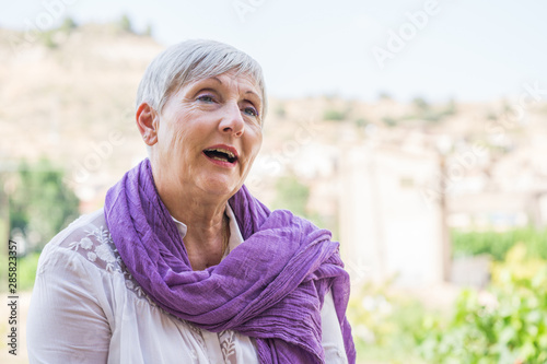 Foto  older woman with purple scarf on her neck and White hair smiling