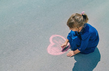 Child Draws With Chalk On The ...