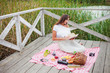 Beautiful young woman in vintage retro clothes has picnic on wooden pier alone. French style picnic outdoors