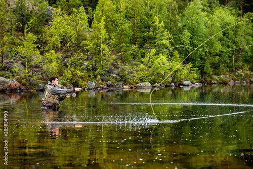 Fisherman using rod fly fishing in mountain river Fototapet