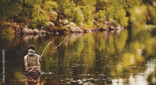 Fisherman using rod fly fishing in river morning sunrise banner Canvas Print