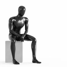 A Black Faceless Mannequin Sit...