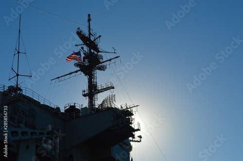 Photo  The sun hides behind a United States warship flying the American flag, throwing