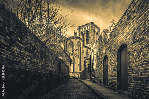 Cuadros en Lienzo YORK, ENGLAND, DECEMBER 13, 2018: cobbled brick street that leads to the magnificent York Minster Cathedral, with narrow red brick walls at both sides