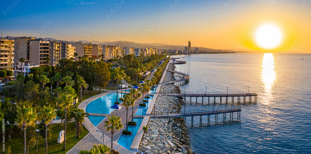 Fototapeta Republic of Cyprus. Limassol. Sunrise over the Mediterranean sea. The Seafront Of Limassol. Walking area with sea view. Early morning in Cyprus. The sun rises over the sea. Promenade.